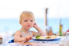 Petite fille mignonne prenant le déjeuner dans le restaurant de station de vacances images stock