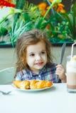 Petite fille mignonne prenant le petit déjeuner avec le croissant dans un restaurant Images libres de droits