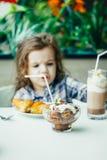Petite fille mignonne prenant le petit déjeuner avec le croissant dans un restaurant Photos stock