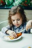 Petite fille mignonne prenant le petit déjeuner avec le croissant dans un restaurant Photo libre de droits