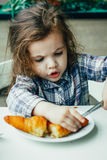 Petite fille mignonne prenant le petit déjeuner avec le croissant dans un restaurant Image stock