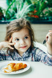 Petite fille mignonne prenant le petit déjeuner avec le croissant dans un restaurant Photographie stock