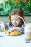 Petite fille mignonne prenant le petit déjeuner avec le croissant dans un restaurant Photos libres de droits