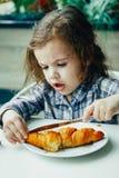 Petite fille mignonne prenant le petit déjeuner avec le croissant dans un restaurant Photographie stock libre de droits