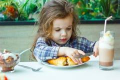 Petite fille mignonne prenant le petit déjeuner avec le croissant dans un restaurant Images stock