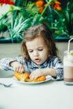 Petite fille mignonne prenant le petit déjeuner avec le croissant dans un restaurant Image libre de droits