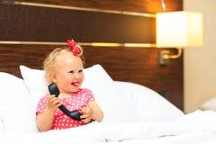 Petite fille mignonne prenant le téléphone dans la chambre d'hôtel Image stock