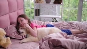 Petite fille mignonne réveillant le chiot somnolent dans la chambre à coucher banque de vidéos