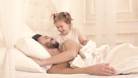 Petite fille mignonne réveillant son père et étreindre banque de vidéos