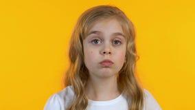 Petite fille mignonne rayant la t?te, essayant de se rappeler l'information, fond d'isolement banque de vidéos