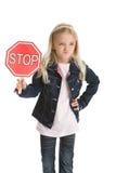 Petite fille mignonne retenant un signe et sourire d'un air affecté d'arrêt Image stock