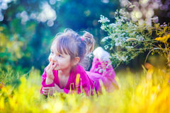 Petite fille mignonne s'étendant dans un domaine Photographie stock libre de droits