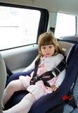 Petite fille mignonne s'asseyant dans la voiture au siège de sécurité pour enfants Photographie stock