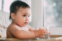 Petite fille mignonne s'asseyant en chaise de b?b? et eau potable  image libre de droits