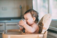 Petite fille mignonne s'asseyant en chaise de b?b? et eau potable  images libres de droits