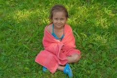 Petite fille mignonne s'asseyant sur l'herbe dans une serviette rose après la natation dans la piscine et le sourire images stock