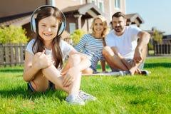 Petite fille mignonne s'asseyant sur l'herbe et la musique de écoute images libres de droits