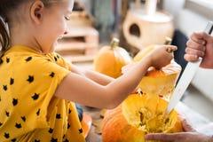 Petite fille mignonne s'asseyant sur la table de cuisine, aidant son père à découper le grand potiron, souriant Antécédents famil image stock