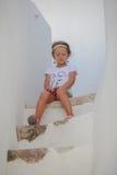 Petite fille mignonne s'asseyant sur les étapes de la vieille maison Photo libre de droits