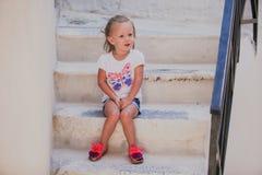 Petite fille mignonne s'asseyant sur les étapes de la vieille maison Photo stock