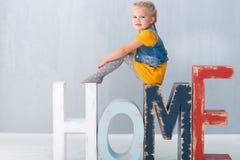 Petite fille mignonne s'asseyant sur les décorations à la maison Photographie stock