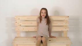 Petite fille mignonne s'asseyant sur un banc dans le studio de mode et posant pour la caméra clips vidéos