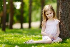 Petite fille mignonne s'asseyant sur un champ de trèfle Photos libres de droits