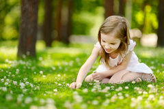 Petite fille mignonne s'asseyant sur un champ de trèfle Image libre de droits