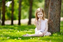 Petite fille mignonne s'asseyant sur un champ de trèfle Photo stock