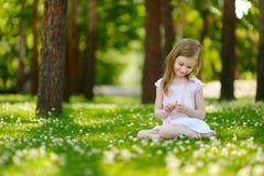 Petite fille mignonne s'asseyant sur un champ de trèfle Photos stock