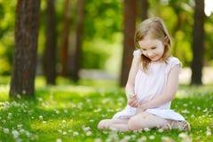 Petite fille mignonne s'asseyant sur un champ de trèfle Photo libre de droits