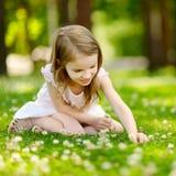 Petite fille mignonne s'asseyant sur un champ de trèfle Images stock