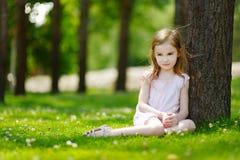 Petite fille mignonne s'asseyant sur un champ de trèfle Images libres de droits