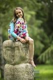 Petite fille mignonne s'asseyant sur un totem en pierre en parc Marche photo libre de droits