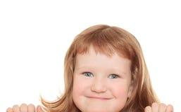 Petite fille mignonne se penchant sur un panneau-réclame Photos stock