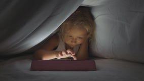 Petite fille mignonne se trouvant sous la couette et à l'aide du dispositif numérique de comprimé à l'heure du coucher banque de vidéos