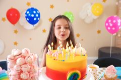 Petite fille mignonne soufflant des bougies sur son gâteau d'anniversaire photographie stock libre de droits