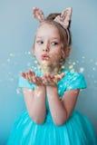 Petite fille mignonne soufflant la poussière magique Image stock