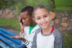 Petite fille mignonne souriant à l'appareil-photo tandis que l'ami parle au téléphone Photo stock