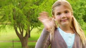 Petite fille mignonne souriant et ondulant banque de vidéos