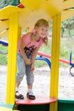Petite fille mignonne sur la cour de jeu extérieure. Photographie stock libre de droits