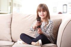 Petite fille mignonne sur le divan Photo stock
