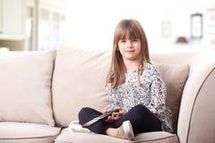 Petite fille mignonne sur le divan Photos libres de droits