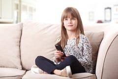 Petite fille mignonne sur le divan Images stock