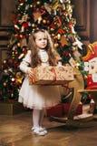 Petite fille mignonne tenant l'arbre et le casse-noix de Noël proches Photo stock