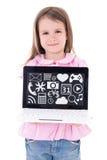 Petite fille mignonne tenant l'ordinateur portable avec les applications et l'icône de media Photographie stock libre de droits