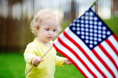 Petite fille mignonne tenant le drapeau américain images libres de droits