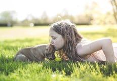 Petite fille mignonne tenant son chien drôle de boxeur Image stock