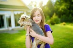 Petite fille mignonne tenant son chien drôle de terrier de Yorkshire Images stock