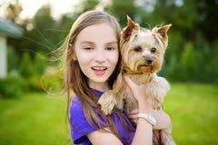 Petite fille mignonne tenant son chien drôle de terrier de Yorkshire Image libre de droits
